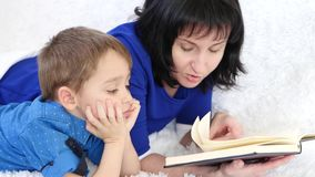 Moder som läser en bok till hennes lilla söner i barnkammaren Lycklig familj, livsstil, barnuppfostran och utbildning av barn lager videofilmer