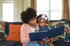 Moder som läser en bok till hennes liten flicka royaltyfri foto