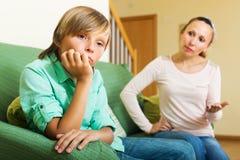 Moder som läxer upp tonåringsonen Arkivfoto