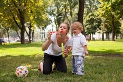 Moder som leker med barnet i parken Royaltyfri Bild