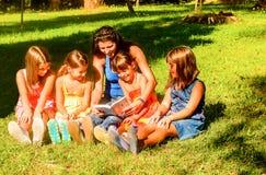 Moder som läser en bok till ungarna Arkivfoto