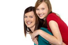 Moder som på ger backen för dotterritt Arkivbild