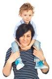 Moder som på ryggen ger ritt till hennes son Arkivbilder