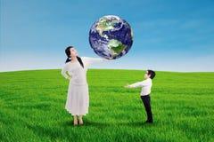 Moder som passerar jorden till hans son Arkivfoto