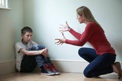 Moder som är fysiskt ovettig in mot son Arkivbild