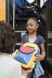 Moder som räcker dotterryggsäcken på skolbussen Royaltyfria Foton