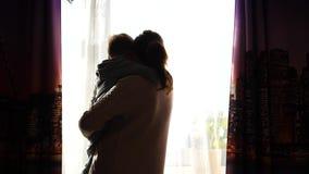 Moder som rymmer ett småbarn på hans händer Solstrålar till och med fönstret Skrattet och glädjen av behandla som ett barn arkivfilmer