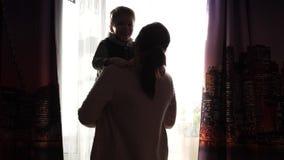 Moder som rymmer ett småbarn på hans händer Solstrålar till och med fönstret Skrattet och glädjen av behandla som ett barn stock video