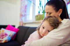 Moder som rymmer hennes lilla ledsna dotter i henne armar Arkivfoton