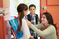Moder som säger farväl till barn, som de lämnar för skola