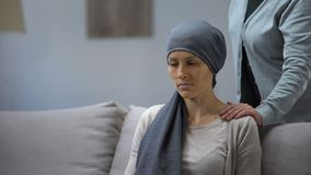 Moder som sätter handen på skuldra av hennes upprivna dotter med cancer, service stock video