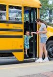 Moder som samlar barnet av skolbussen Royaltyfri Bild