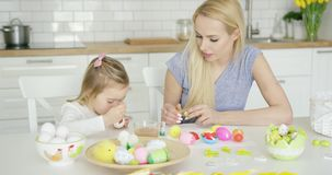 Moder som ser flickafärgläggningägg lager videofilmer