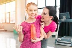 Moder som ser le den hållande sportflaskan för dotter med vatten i idrottshall Royaltyfri Foto