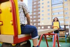 Moder som spelar med sonen på lekplats Royaltyfri Foto