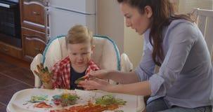 Moder som spenderar tid samman med barnet som drar med färgmålarfärger arkivfilmer