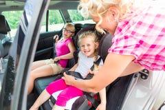 Moder som spänner fast upp på barn i bil Fotografering för Bildbyråer