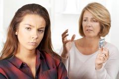 Moder som talar till den tonårs- dottern om det att använda preventivmedel Royaltyfri Bild