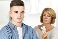 Moder som talar till den tonårs- sonen om det att använda preventivmedel Royaltyfri Bild