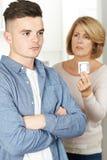 Moder som talar till den tonårs- sonen om det att använda preventivmedel Arkivfoto