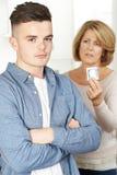 Moder som talar till den tonårs- sonen om det att använda preventivmedel Arkivfoton
