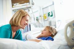 Moder som talar till dottern i intensivvårdenhet Arkivfoto