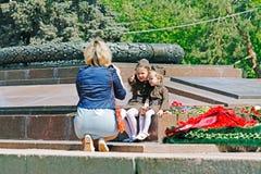 Moder som tar bilder av döttrar som kläs som rysk sovjetisk soldat av världskrig II på evig brand på segerdag i Volgograd arkivfoton