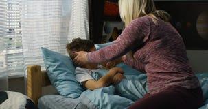 Moder som tar omsorg av den sjuka sonen lager videofilmer