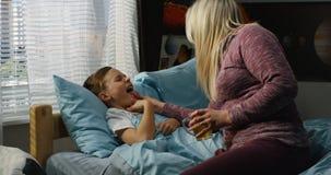Moder som tar omsorg av den sjuka sonen arkivfoto