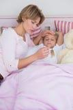 Moder som tar temperaturen av den sjuka dottern Arkivfoton