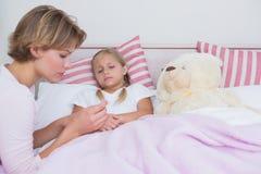 Moder som tar temperaturen av den sjuka dottern Royaltyfri Bild