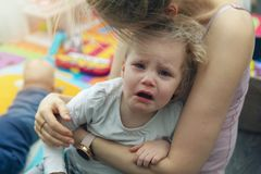 Moder som tröstar hennes skriande lilla barn royaltyfri fotografi