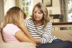 Moder som tröstar sammanträde för tonårs- dotter på Sofa At Home royaltyfria foton