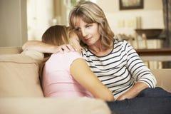 Moder som tröstar sammanträde för tonårs- dotter på Sofa At Home royaltyfri foto