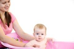 Moder som tvättar en behandla som ett barn i rosa badkar Arkivfoto