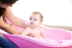 Moder som tvättar en behandla som ett barn i rosa badkar Royaltyfri Foto