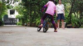 Moder som undervisar hennes barn att rida en cykel arkivfilmer