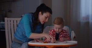 Moder som undervisar hur man räknar hennes barn med fingrar och kulöra blyertspennor lager videofilmer