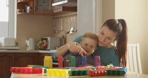 Moder som undervisar Little Boy hur man räknar genom att använda kulöra kvarter och genom att använda bildande lekar arkivfilmer