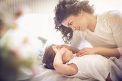 Moder som upp vaknar dottern lycklig morgon royaltyfri foto