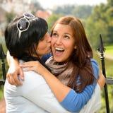Moder som utomhus kysser henne lycklig omfamning för dotter royaltyfri foto