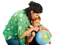 Moder som visar till sonen på världsjordklotet Arkivfoton