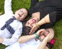 Moder, son och dotter Lauging utanför i gräset Royaltyfri Foto