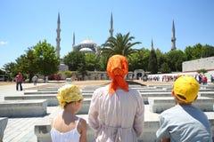 Moder, son och dotter som går till den Sultanahmet moskén Arkivbild