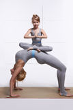Moderdotter som gör yogaövningen, kondition, idrottshall som bär de samma bekväma träningsoverallerna, familjsportar, parade spor Arkivfoton