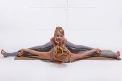 Moderdottern som gör yogaövningen, konditionfamiljsportar, sportar parade kvinnasammanträde på golvet som ifrån varandra sträcker royaltyfri fotografi