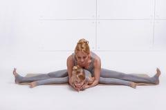 Moderdottern som gör yogaövningen, konditionfamiljsportar, sportar parade kvinnasammanträde på golvet som ifrån varandra sträcker royaltyfri bild