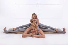 Moderdottern som gör yogaövningen, konditionfamiljsportar, sportar parade kvinnasammanträde på golvet som ifrån varandra sträcker arkivbild