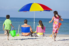 Moderfader & barnfamilj på strand Arkivbild