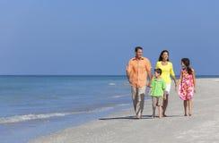 Moderfader och barnfamilj som går på stranden Arkivbilder